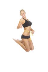 Frau misst ihren Bauchumfang und springt  vor Freude in die Luft