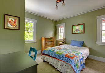 Kids bedroom with desk and green walls.