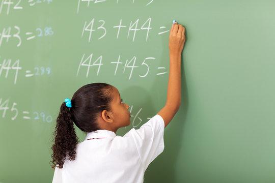primary school girl writing maths answer on chalkboard