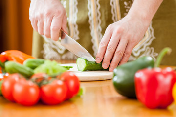 Preparing actions for vegetable salad on kitchen table. Focus on