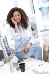 Pretty office worker on mobile phone smiling