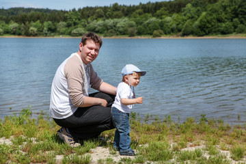 Young man with toddler boy on lake in summer