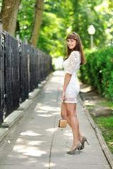 Full length portrait of a beautiful woman in white dress walking