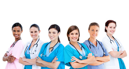 Smiling female hospital workers standing arms folded in line