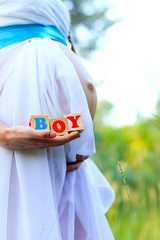 Close-up of the belly of a pregnant woman  holding boy cubes out