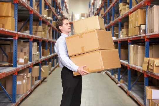 Man Carrying Boxes In Warehouse