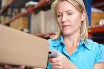 Businesswoman Scanning Package In Warehouse