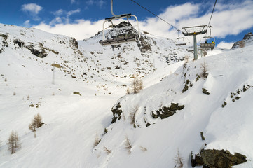 chairs on ski lift above a rocky mountain in winter