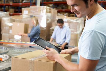 Worker Using Tablet Computer In Distribution Warehouse