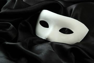 White mask, on black silk fabric