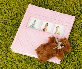 Baby photo album on green carpet