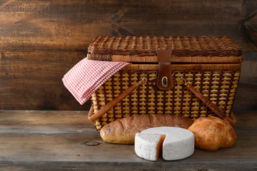 Foto op Aluminium Picknick picnic basket with bread and cheese on wood