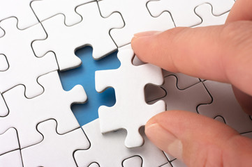 A person fitting the last puzzle piece.