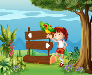 A parrot and a girl beside a signboard in the forest