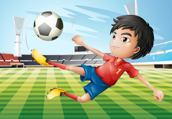A boy playing soccer at the soccer field