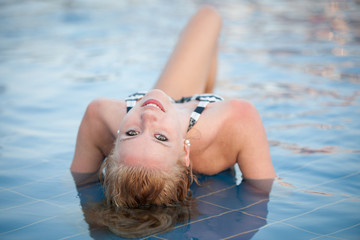 Attractive blonde girl in bikini swimwear  in swimming pool on l
