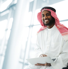 Black Arabic man working on laptop