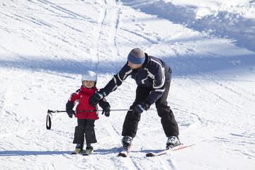 Kind mit Erwachsenen beim Skifahren lernen