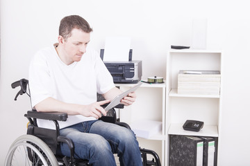 young man in wheelchair using a tablet pc