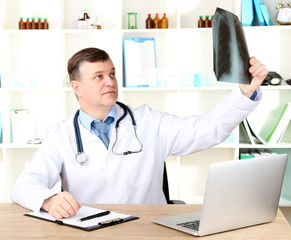 Medical doctor analysing x-ray image at desk