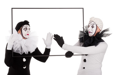 Zwei Pantomimen berühren einen leeren Bilderrahmen