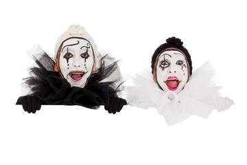 Zwei Clowns blicken strahlend über eine Kante