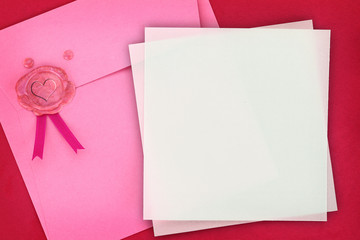 Paper envelope with heart sealing wax stamp and invitation card