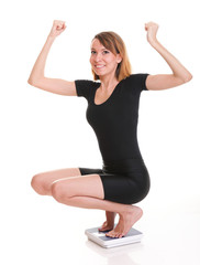 Portrait of a happy woman squatting on scales isolated