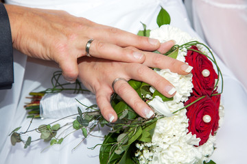Hands with wedding rings and bridal bouquet