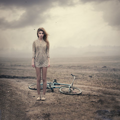 beautiful girl and a bike in the countryside on a cloudy day