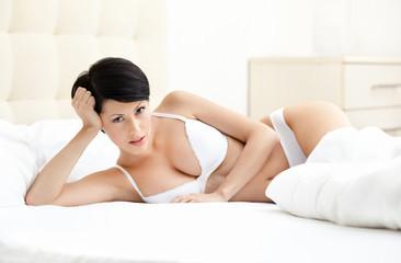 Woman in bra is lying in the queensize bed