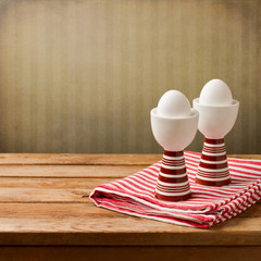 Easter background with eggs on wooden table over retro wallpaper