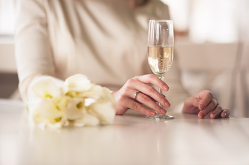 Bride and groom holding wedding glasses with champagne