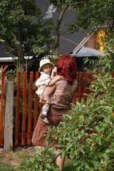 Frau mit Kind beim Gespräch am Gartenzaun