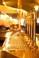 Fototapete - waiter is drafting a beer from a golden spigot