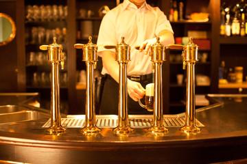 Wall Mural - waiter is drafting a beer from a golden spigot