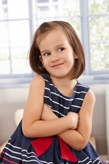 Impish little girl smiling arms crossed
