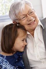 Grandmother and little girl smiling and hugging