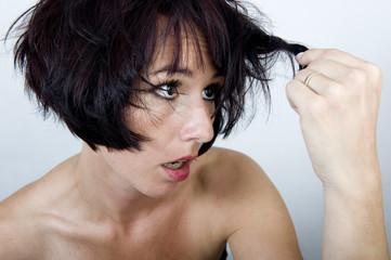 Kobieta spoglądająca na swoje niepoukładane włosy
