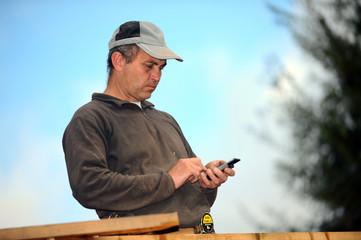 Carpenter sending text message whilst working outdoors