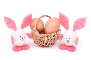 basket with Easter eggs and two rabbits isolated on white