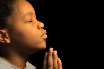 Praying African American boy