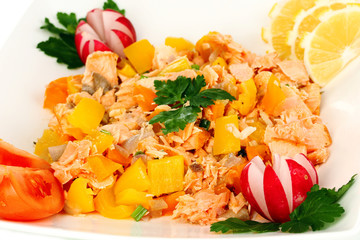 Appetizing sliced salmon with lemon and vegetables close up