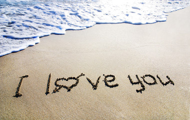 """words """"I love you"""" outline on the wet sand with the wave brillia"""