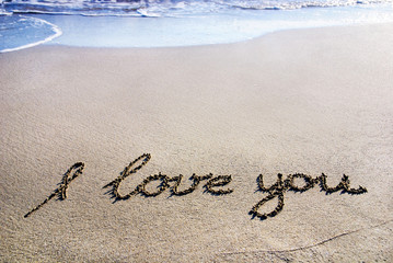 "words ""I love you"" outline on the wet sand with the wave brillia"