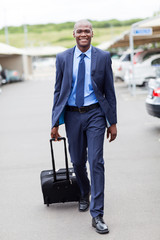 handsome african businessman walking in airport parking lot