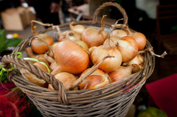 Rustic basket full of ripe onions at local market