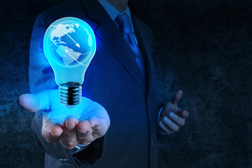 Businessman hand shows Light bulb with planet Earth social netwo