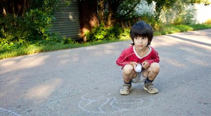 boy drawing on asphalt