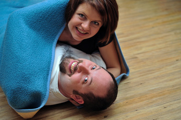 Happy couple wrapped in blue blanket